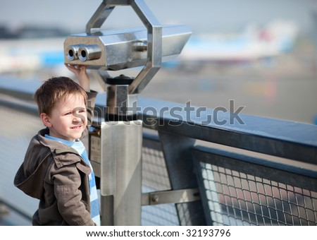 Boy with telescope on panorama terrace in airport. - stock photo