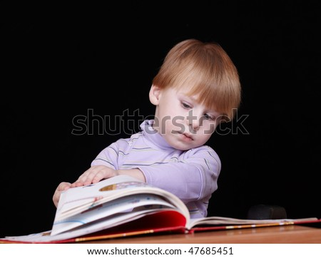boy with the book behind a table on the black background