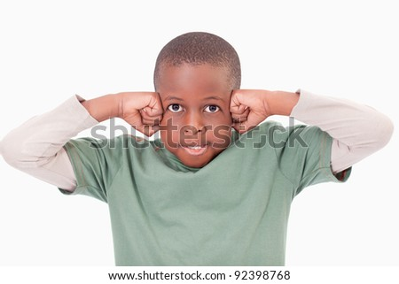 Boy with the fists on his face against a white background - stock photo