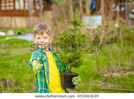 boy with tree seedling showing thumb up