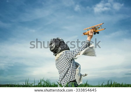 Boy with wooden airplane outdoors - stock photo