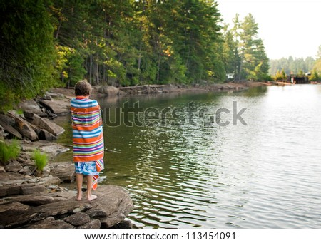 boy wrapped in a beach towel at a lake in Haliburton County - stock photo