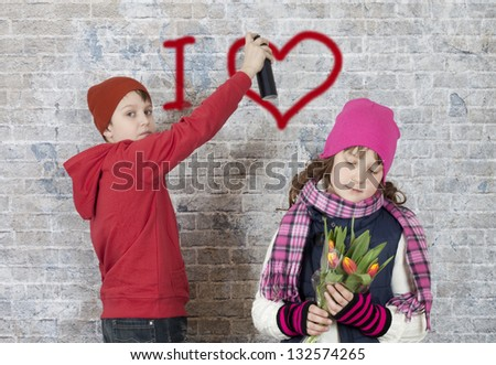 """Boy writing """"I love"""" on a brick wall while girl looking at flowers - stock photo"""