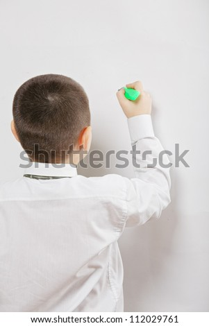 Boy writing on whiteboard with green marker rear view