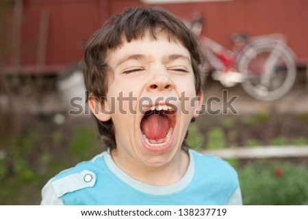 boy yawning on the country background