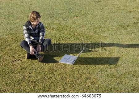 Boy, 15 years, online on his laptop in the park - stock photo