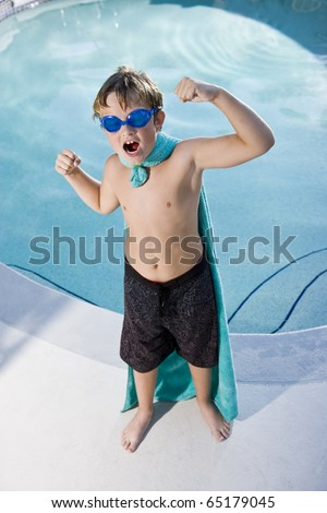 Boy, 9 years, playing by swimming pool in pretend superhero costume flexing muscles
