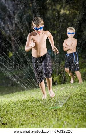 Boy, 9 years, running through water spray from lawn sprinkler - stock photo