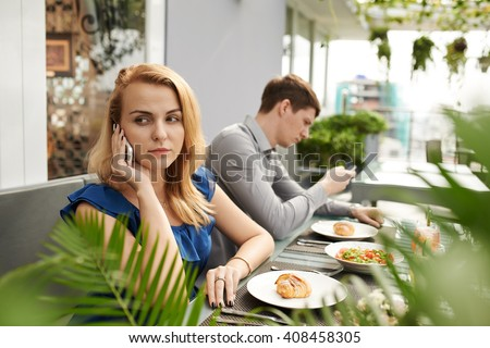 Boyfriend and girlfriend busy with smartphone during date in cafe - stock photo