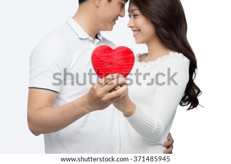 Boyfriend and girlfriend kissing with happy face expression looking each other in eyes. Couple of asian lovers at the beginning of love story having fun together. - stock photo