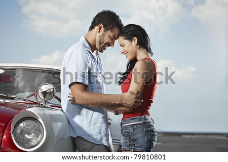 boyfriend and girlfriend leaning on vintage car and hugging in havana, cuba. Horizontal shape, side view, copy space - stock photo