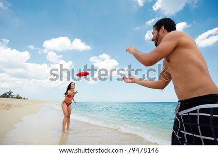 boyfriend and girlfriend playing with frisby on tropical beach. Horizontal shape, copy space - stock photo