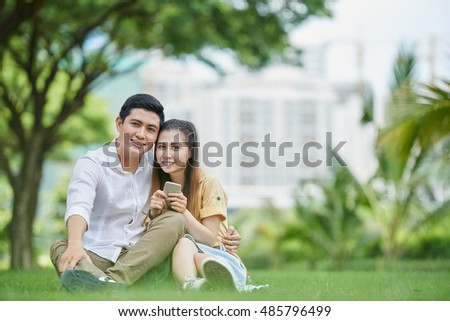 Boyfriend and girlfriend resting in park with smartphone
