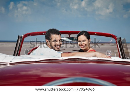 boyfriend and girlfriend sitting in vintage car and hugging in havana, cuba. Horizontal shape, side view, copy space - stock photo