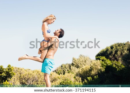 Boyfriend carrying his girlfriend by the pool - stock photo