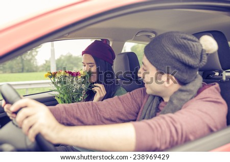 boyfriend giving a bucket of flowers to his girlfriend in the car. she smells her and looks happy - stock photo