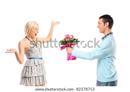 Boyfriend giving flowers to his surprised girlfriend isolated against white background - stock photo