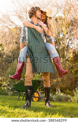 Boyfriend giving piggy back to girlfriend in the garden - stock photo