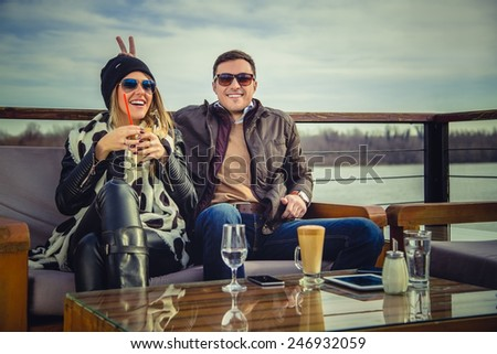 Boyfriend holding bunny ears to his girlfriend - stock photo