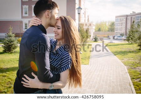 Boyfriend kiss her girlfriend hugging him city background. Strong Back light and lens flare  - stock photo