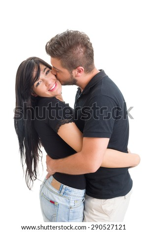Boyfriend kissing girlfriend on the cheek on white studio background - stock photo