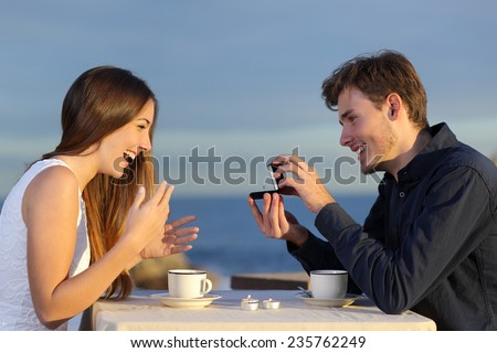 Boyfriend requesting hand of his girlfriend with a engagement ring in a restaurant with the ocean in the background - stock photo