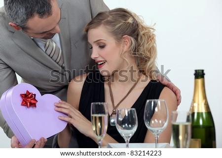 Boyfriend surprising girlfriend with heart-shaped box - stock photo