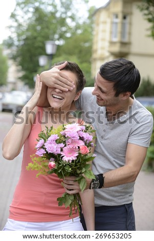 Boyfriend surprising his girlfriend with a  bouquet of flowers - stock photo