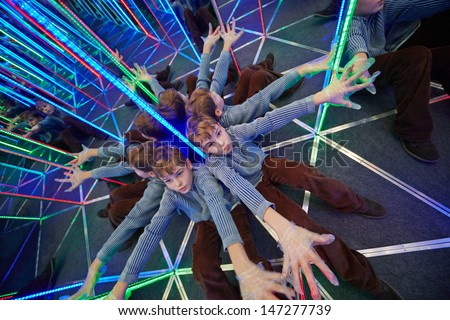 Boyl sits stretching his arms at crossing in mirror labyrinth illuminated with color lights - stock photo