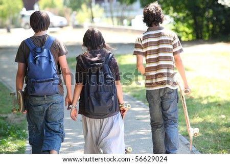 Boys and girl with backpacks and skateboards having a walk - stock photo
