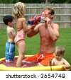 Boys and girl with dad in the kiddie pool. - stock photo