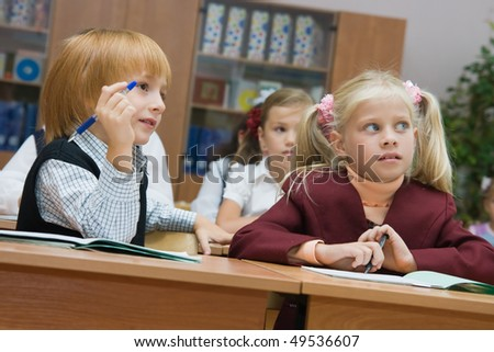 Boys and girls at a lesson at school sit at school desks - stock photo