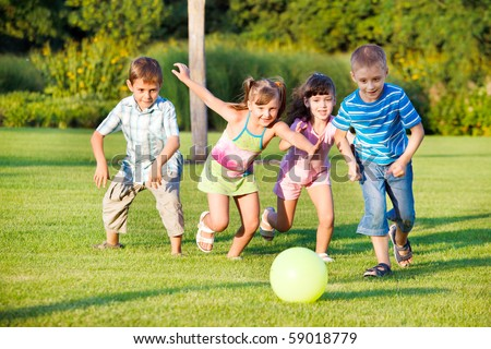 Boys and girls running towards ball - stock photo
