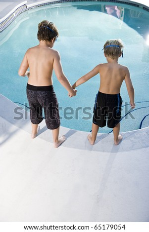 Boys, 7 and 9, looking down at water in swimming pool - stock photo