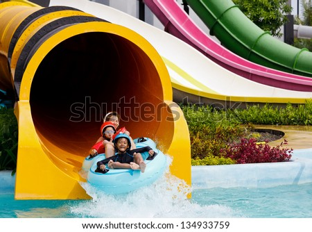 Boys and mother playing in water park in summer