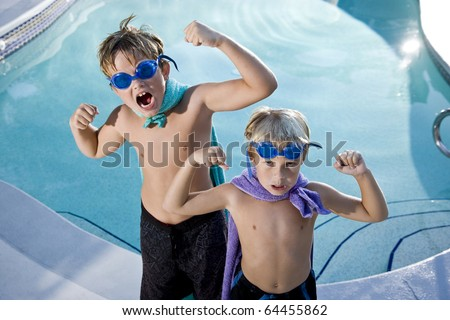 Boys, 7 and 9, playing superhero by swimming pool, flexing muscles - stock photo