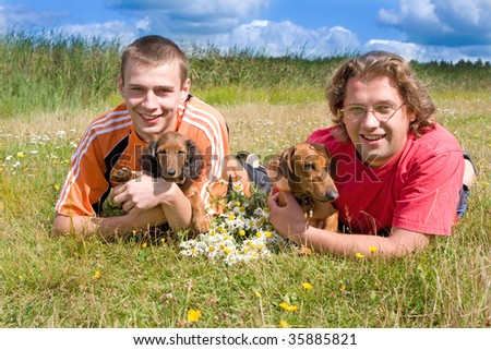 boys and the little dog on the grass and flowers daisies