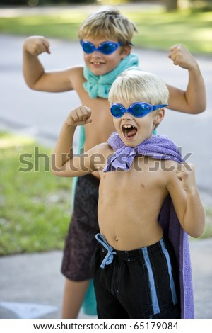 Boys, 7 and 9 years, flexing muscles in superhero costumes, focus on boy shouting - stock photo