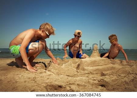 Boys at play on sea beach - stock photo