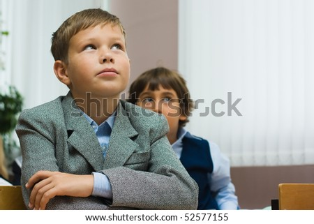 Boys at school sit at school desks and attentively look upwards - stock photo