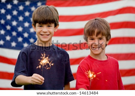 Boys at Twilight Holding Sparklers in Front of Flag - stock photo