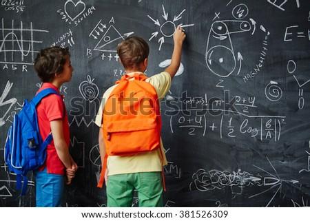 Boys by blackboard - stock photo