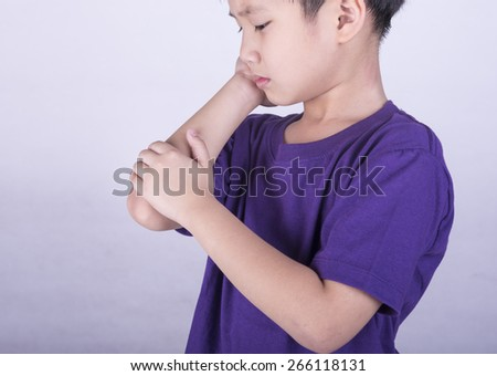 Boys checking his arm with muscle pain. - stock photo