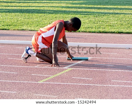 boys club track runner preparing for a relay race - stock photo