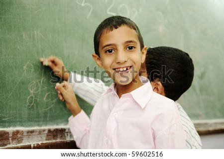 Boys drawing and writing on board in school - stock photo