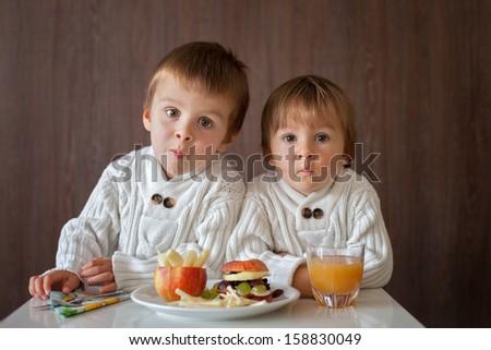 Boys, eating fruit sanwich - stock photo