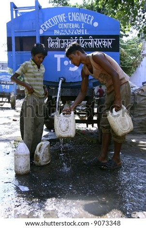 boys filling water in cans, delhi, india - stock photo
