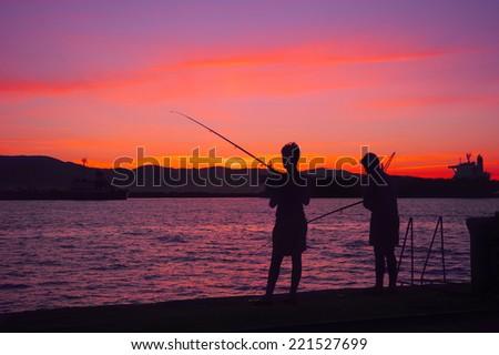 Boys fishing at dusk - stock photo
