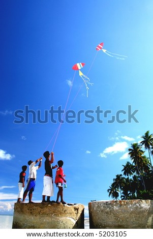 boys flying kites on sunny and windy day - stock photo