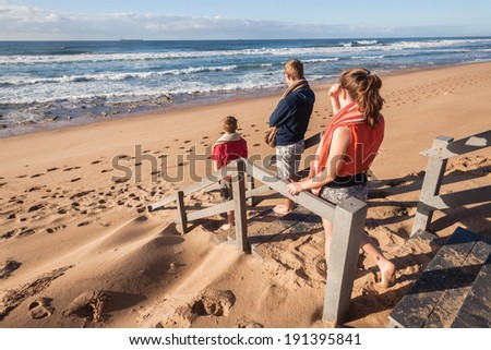 Boys Girl Beach Stairs Ocean Teen girl and boys standing on stairs overlooking beach ocean wave landscape - stock photo